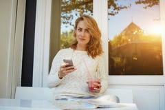 Estudiante joven atractivo que usa el teléfono móvil mientras que goza de la bebida de la fruta en tienda acogedora del coffe, Fotos de archivo libres de regalías