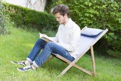 Estudiante joven barbudo serio que lee un libro en el jardín Imagenes de archivo