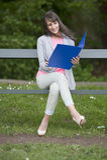 Estudiante joven con el fichero asentado en un banco, al aire libre Foto de archivo libre de regalías