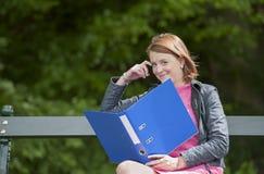 Estudiante joven con el fichero asentado en un banco, al aire libre Imágenes de archivo libres de regalías
