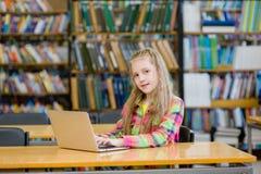 Estudiante joven con el ordenador portátil en biblioteca Fotografía de archivo