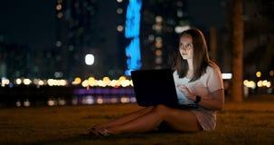 Estudiante joven con el ordenador portátil en la noche en texto que mecanografía de la ciudad almacen de video