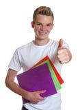 Estudiante joven con el papeleo que muestra el pulgar Foto de archivo