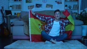 Estudiante joven con la bandera española que apoya el equipo nacional, campeonato del fútbol almacen de metraje de vídeo