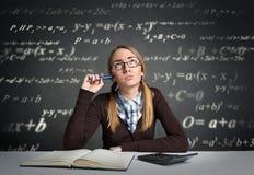 Estudiante joven con la expresión pensativa que se sienta en un escritorio Fotos de archivo libres de regalías