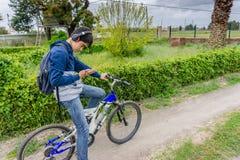 Estudiante joven con la mochila y la bicicleta, escuchando la música Fotos de archivo libres de regalías