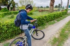 Estudiante joven con la mochila y la bicicleta, escuchando la música Imagen de archivo libre de regalías