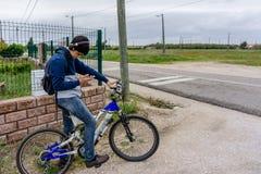 Estudiante joven con la mochila y la bicicleta, escuchando la música Fotografía de archivo