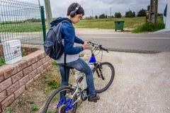 Estudiante joven con la mochila y la bicicleta, escuchando la música Imagenes de archivo
