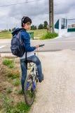 Estudiante joven con la mochila y la bicicleta, escuchando la música Fotos de archivo