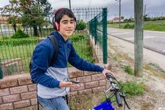 Estudiante joven con la mochila y la bicicleta, escuchando la música Foto de archivo
