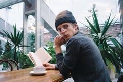 Estudiante joven con los vidrios que bebe té y que lee un libro en un café agradable durante una rotura en la universidad Foto de archivo libre de regalías