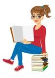 Estudiante joven con los vidrios que se sientan en la pila de libros que muestran el libro de texto abierto Foto de archivo