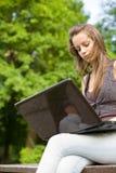 Estudiante joven con su computadora portátil al aire libre. Foto de archivo libre de regalías