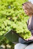 Estudiante joven con su computadora portátil al aire libre. Imagenes de archivo