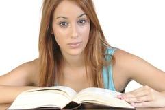 Estudiante joven con un libro abierto en el fondo blanco Fotos de archivo libres de regalías