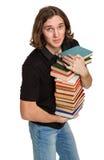 Estudiante joven con una pila de libros Foto de archivo libre de regalías