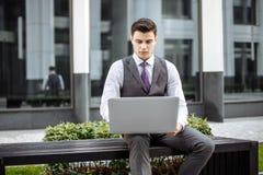 Estudiante joven de la Escuela de Negocios que trabaja en un ordenador portátil mientras que se sienta en un banco Imágenes de archivo libres de regalías