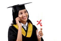 Estudiante joven de la graduación que habla en el teléfono móvil Imagenes de archivo
