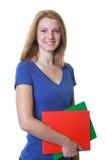 Estudiante joven de risa con el pelo y los libros rojos Fotos de archivo libres de regalías