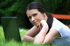 Estudiante joven de YBeautiful que usa el ordenador portátil en hierba Foto de archivo