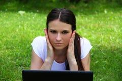 Estudiante joven de YBeautiful que usa el ordenador portátil en hierba Fotos de archivo libres de regalías