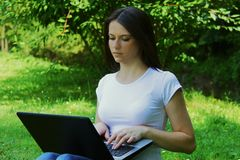 Estudiante joven de YBeautiful que usa el ordenador portátil en hierba Fotografía de archivo libre de regalías