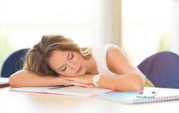 Estudiante joven dormido en la tabla fotos de archivo