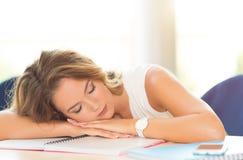 Estudiante joven dormido en la tabla fotos de archivo libres de regalías