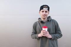 Estudiante joven elegante en un casquillo en un fondo ligero con una taza de bebida caliente en sus manos Foto de archivo