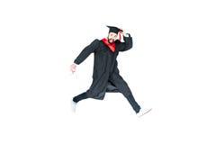 Estudiante joven en el casquillo de la graduación con el salto del diploma aislado Fotos de archivo libres de regalías