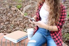 Estudiante joven en el parque con la tableta, el café y libros Fotografía de archivo