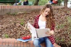 Estudiante joven en el parque con la tableta, el café y libros Fotografía de archivo libre de regalías