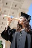 Estudiante joven en el vestido que mira a través del diploma Fotografía de archivo