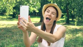 Estudiante joven en la camisa blanca que se sienta en hierba en el campus de la universidad que hace el selfie en el teléfono móv almacen de metraje de vídeo