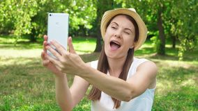 Estudiante joven en la camisa blanca que se sienta en hierba en el campus de la universidad que hace el selfie en el teléfono móv almacen de video
