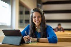 Estudiante joven en la sala de clase de la universidad Ella ` s usando la tableta y los auriculares para tomar notas Imagen de archivo