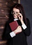 Estudiante joven en vidrios con los libros a disposición, misterioso mirando la cámara Fotografía de archivo libre de regalías