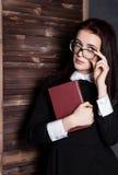Estudiante joven en vidrios con los libros a disposición, misterioso mirando la cámara Imágenes de archivo libres de regalías