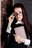 Estudiante joven en vidrios con los libros a disposición, misterioso mirando la cámara Imagenes de archivo