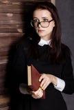 Estudiante joven en vidrios con los libros a disposición, misterioso mirando la cámara Foto de archivo libre de regalías