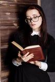 Estudiante joven en vidrios con los libros a disposición, misterioso mirando la cámara Fotos de archivo libres de regalías