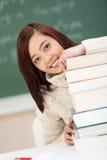 Estudiante joven feliz con una pila de libros de texto Imagen de archivo