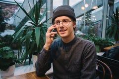 Estudiante joven feliz que habla en el teléfono en la ventana que pasa por alto la terraza con las plantas verdes Foto de archivo
