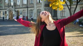 Estudiante joven feliz sacudiendo su pelo y riendo, mirando en una cámara, colocándose en el fondo de la universidad almacen de metraje de vídeo