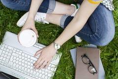 Estudiante joven femenino usando el ordenador port?til en aire libre fotografía de archivo