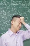 Estudiante joven frustrado delante de la pizarra con las ecuaciones de la matemáticas que llevan a cabo la cabeza Fotografía de archivo libre de regalías