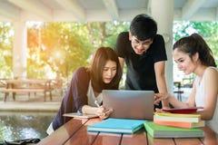 Estudiante joven Group Holding Book y sonrisa del ordenador portátil Foto de archivo libre de regalías