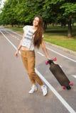 Estudiante joven hermoso con el pelo largo que coloca y que sostiene un longboard en el camino en el parque skateboarding outdoor Foto de archivo
