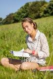 Estudiante joven hermoso que lee un libro en el parque Fotos de archivo